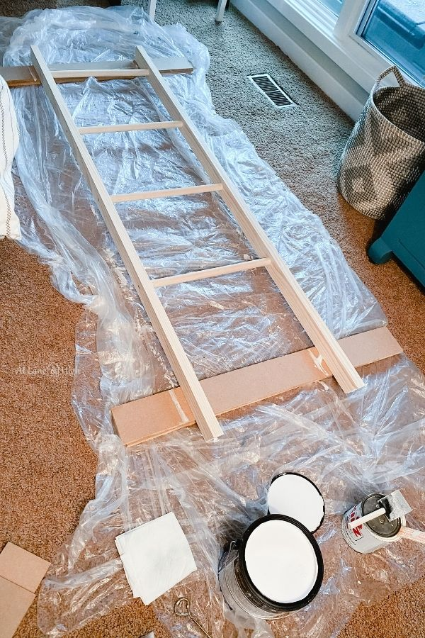 The blanket ladder on the floor with plastic under prepped for painting.