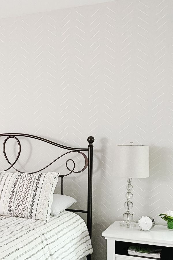 The finished focal wall with the herringbone stencil, a black metal headboard.