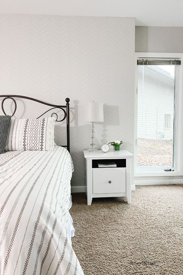 The right side of the bed and the wall with a bedside table that has a lamp, silver clock and a small vase of white roses.