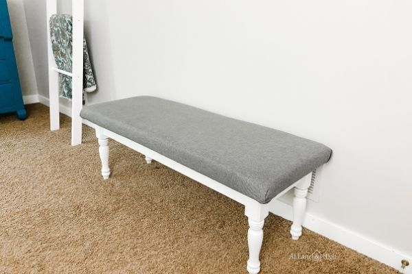 The finished bench with a white painted base and gray fabric top.