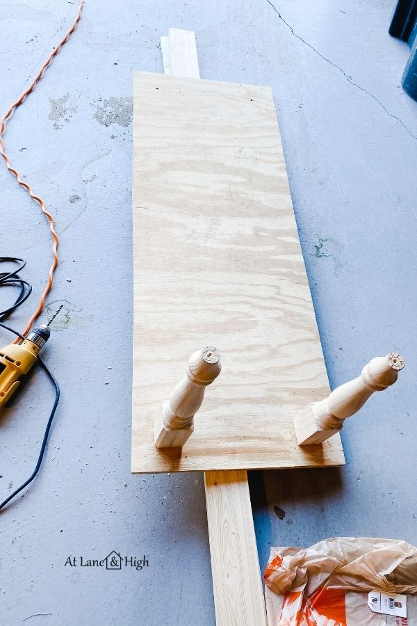 Two table legs have been attached to the plywood.