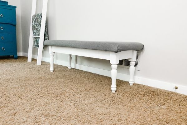 The finished bench with a white painted base and a gray fabric top.