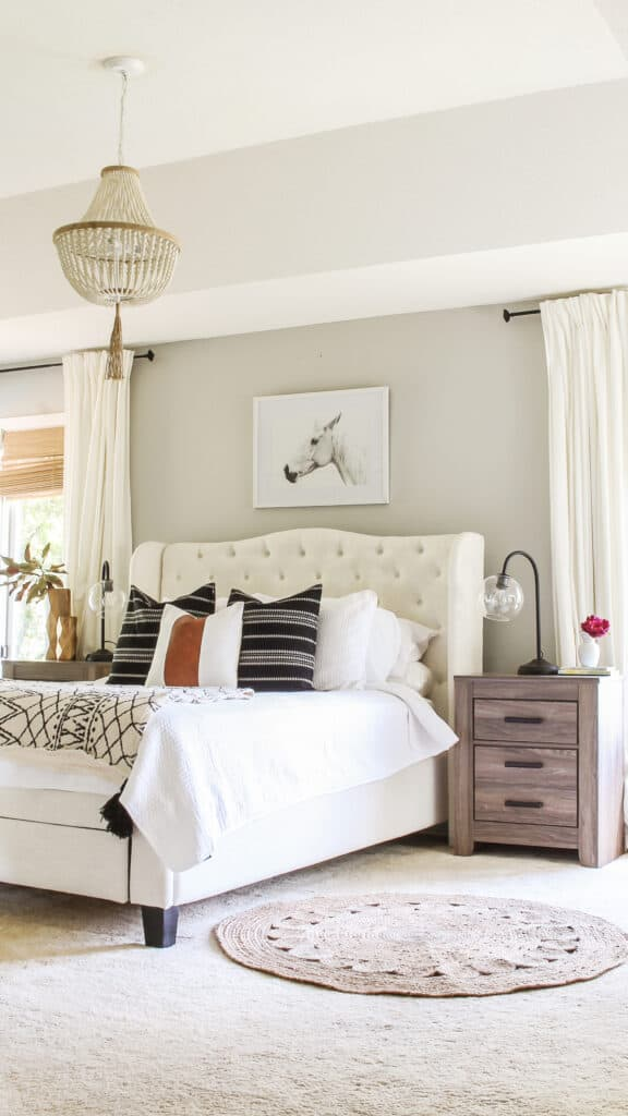A bedroom with Repose Gray walls, a tufted white headboard, white curtains, gray stained furniture and a horse artwork above the headboard.