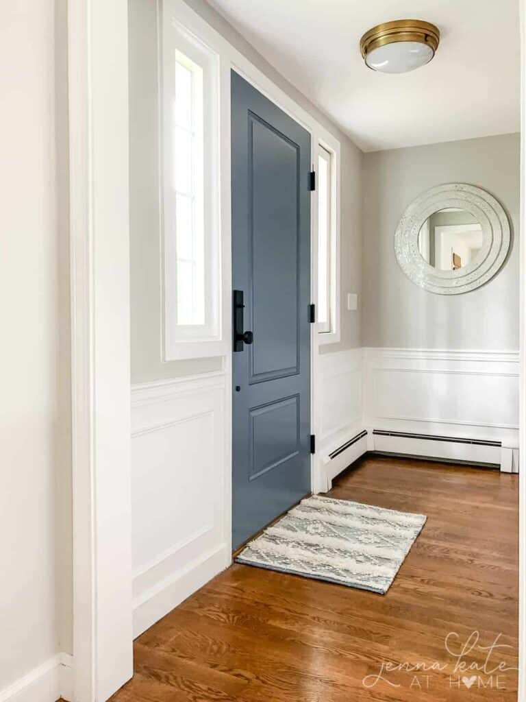 An entryway with white wainscoting, repose gray on the walls, and a blue door.