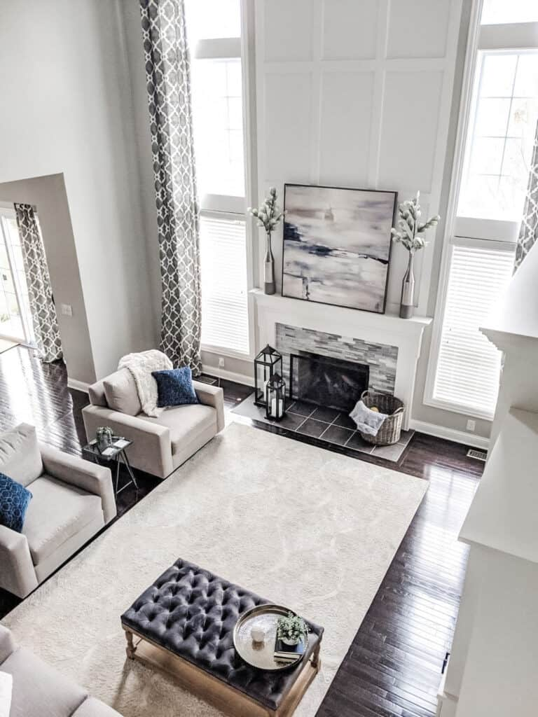 A family room with soaring vaulted ceilings.  White panelling above the fireplace pops next to the gray color of Repose Gray.