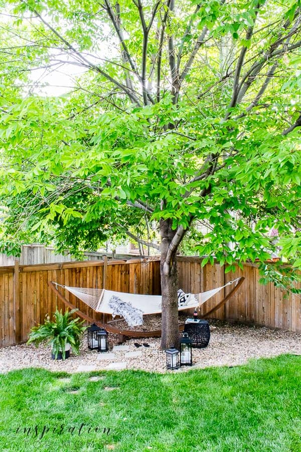A hammock under a tree in the corner of the backyard against a fence.