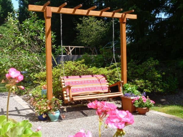 A bench swing hung from a pergola with flower pots all around.