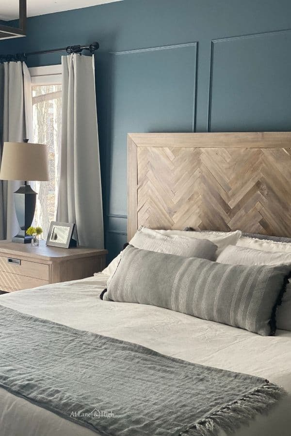 DIY Herringbone Headboard agains a smokey blue wall with picture molding.