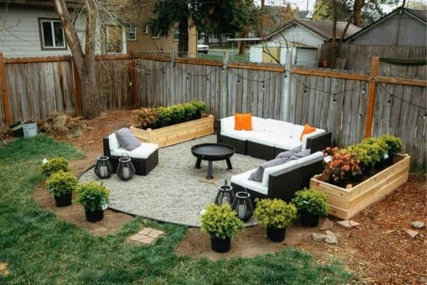 A fire pit surrounded by couches and raised garden beds with string lights on the fence behind.