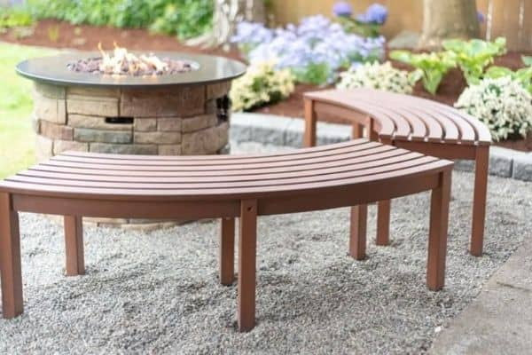This pea gravel patio area has curved benches and a fire pit.