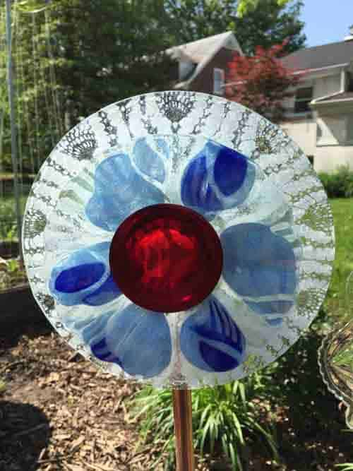 Old dishes that were glued together to create yard decor flowers.