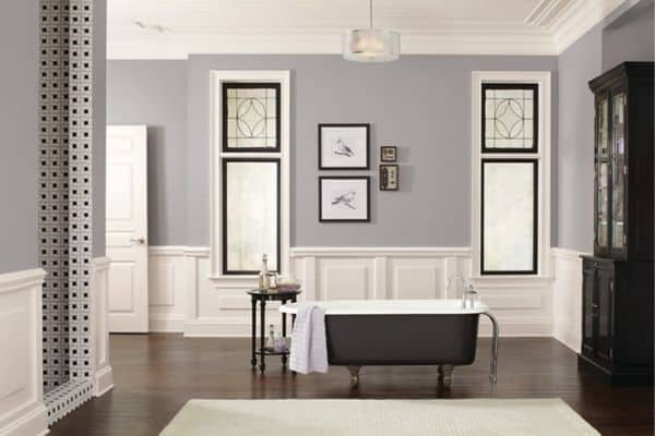 Passive used on the wall sin a bathroom with dark wood floors, white wainscoting and black trimmed windows.