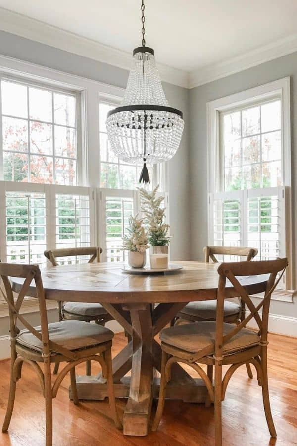 Passive in the dining room with tons of windows, wood table and chairs and a crystal beaded chandelier.