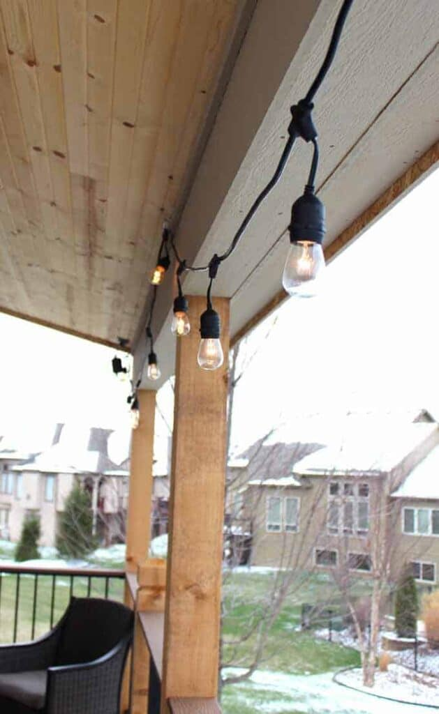 A deck with string lights hanging on the edge.