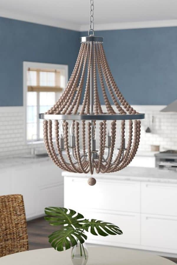 A gray beaded chandelier in a kitchen over a breakfast table.