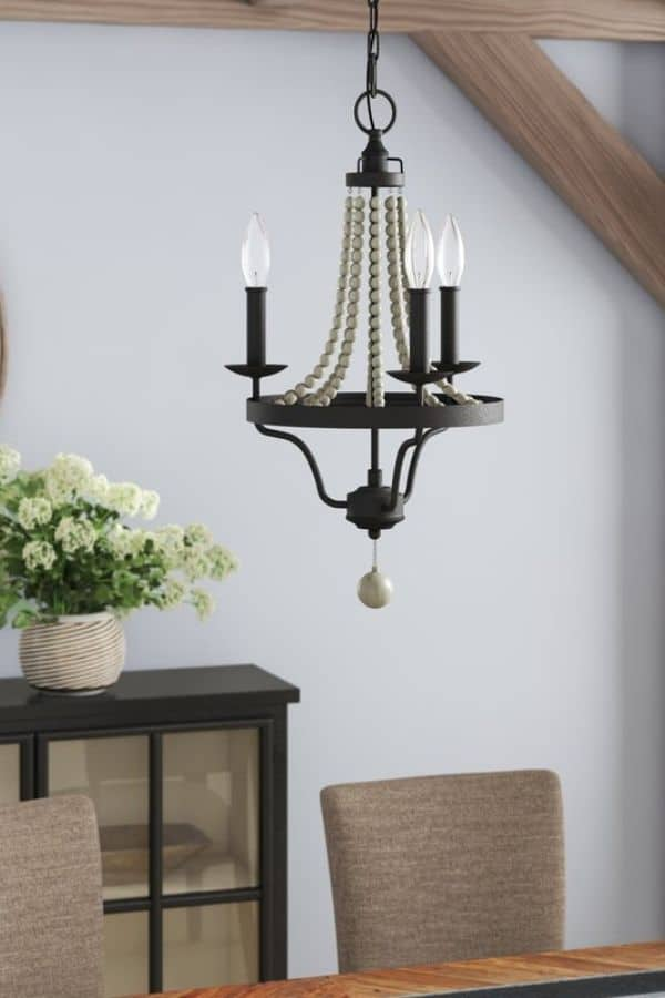 A smaller light fixture with light gray beads and dark metal.