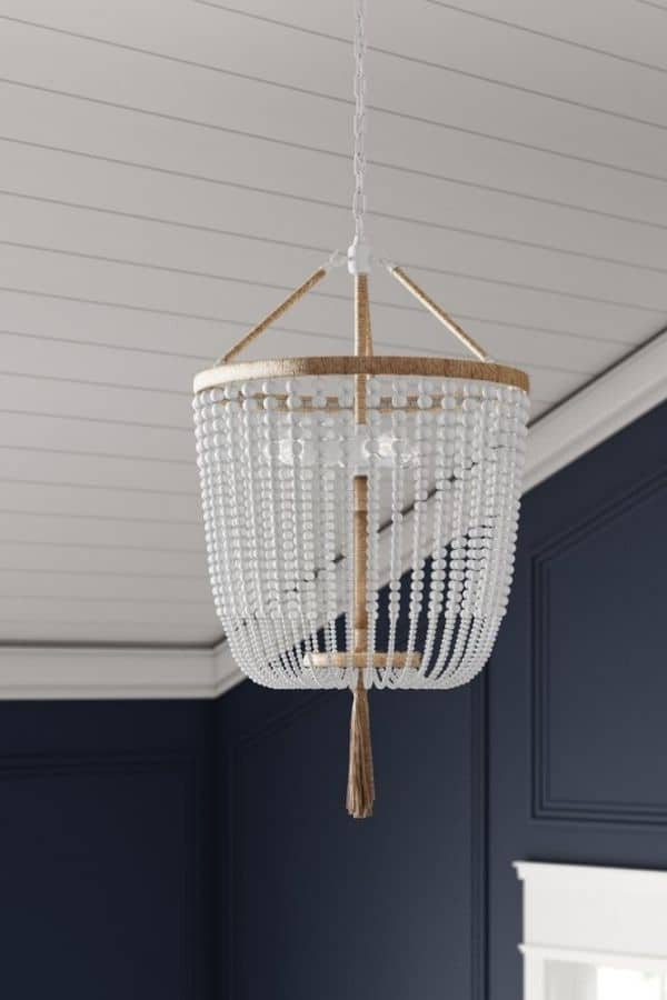 A white beaded chandelier with a tassel hanging from the bottom.