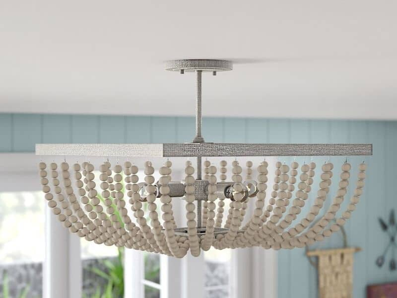 A white metal chandelier with white beads on a semi flush mount fixture.