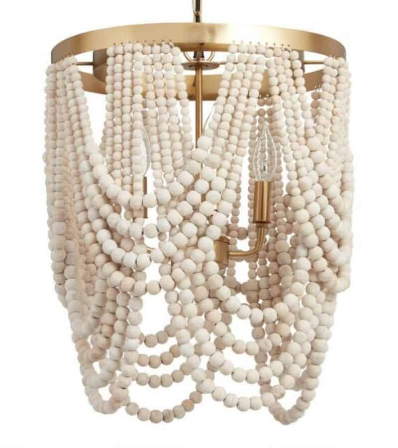 A white beaded drapey chandelier with gold metal.