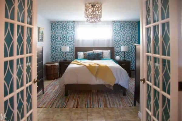 A bedroom with a stenciled headboard wall and diy light fixture.