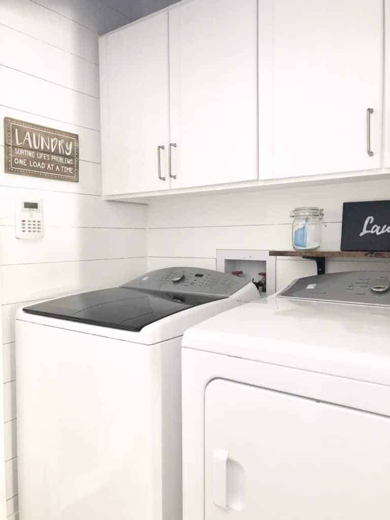 A laundry room with white painted shiplap walls and white cabinets.
