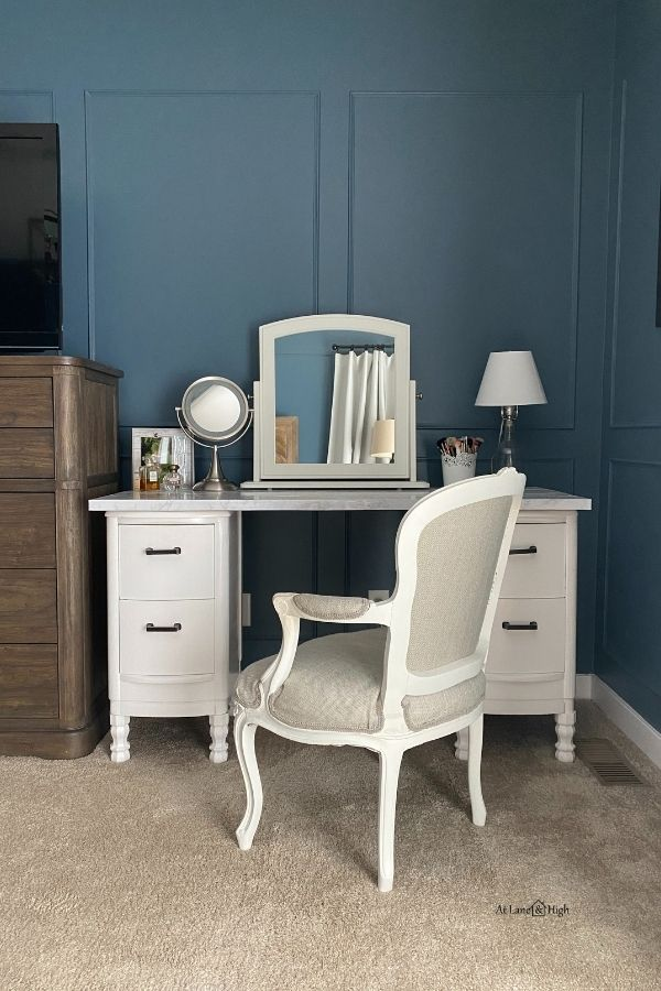 My white vanity against the smokey blue walls with picture frame molding.