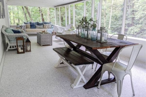 A screened in porch with a picnic table and a sofa seating area.