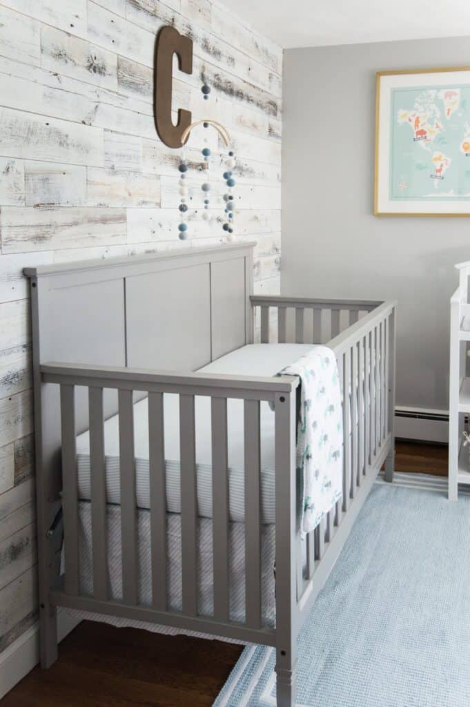 A nursery with a gray crib that matches the Stonington Gray walls and a white washed reclaimed wood wall.