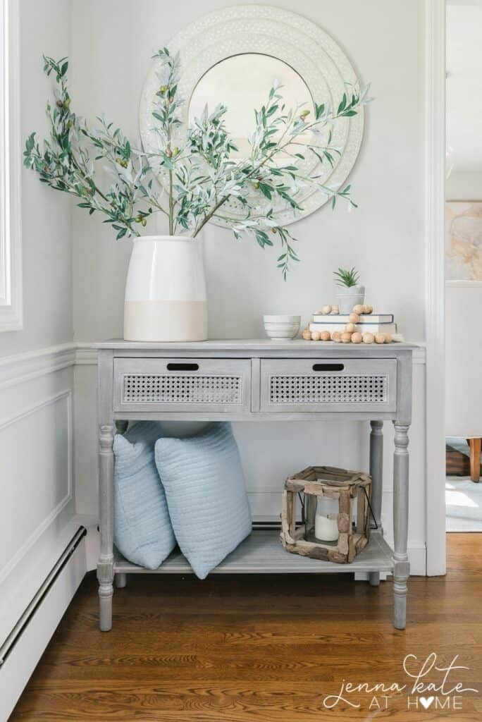 An example of Stonington Gray in an entry with a gray wash console table and a large vase with olive branches in it.