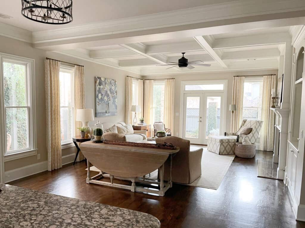 A family room with coffered ceilings, tons of windows and accessible beige on the walls.