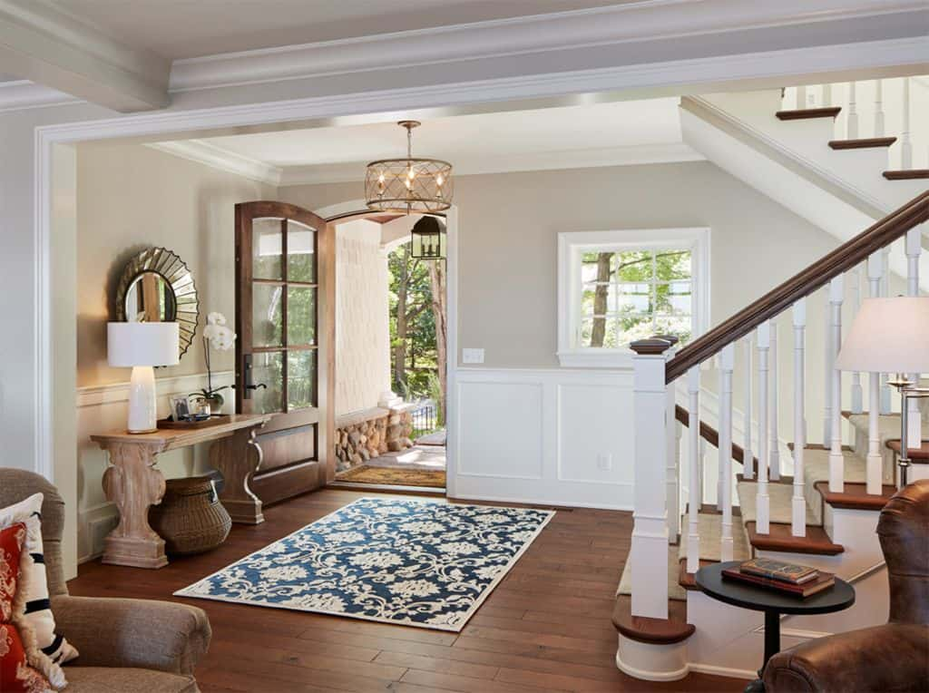 This is an entryway with dark brown floors, white board and batten and accessible beige on the walls.