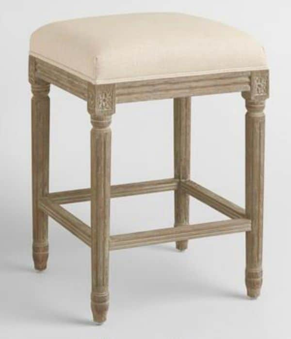 Brownish Gray distressed wood stool with a light beige linen seat that has no back.