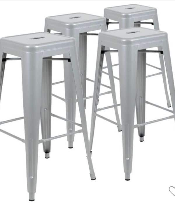 Gray metal bar stools that can be stacked on one another.