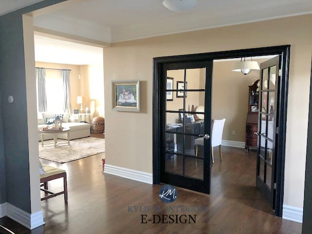 Stone House on the walls of an entryway with black glass doors to an office and white trim with dark hardwood floors.