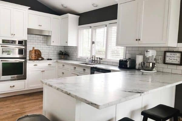A white kitchen with silver drawer pulls, gray walls and black wood stools.