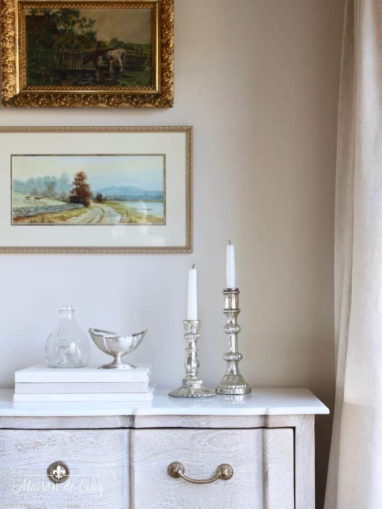 A close up of walls with Muslin paint and artwork on them over a console table.
