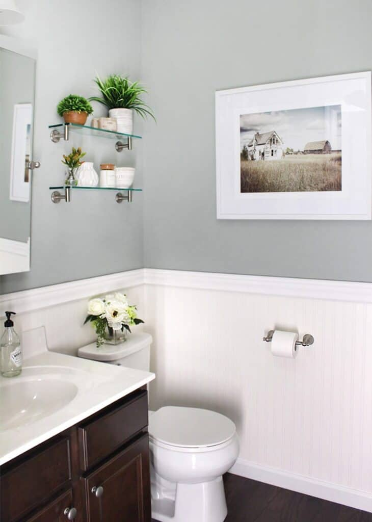 A powder room with white wainscoting on the bottom half of the walls and Oyster Bay painted on the top half.