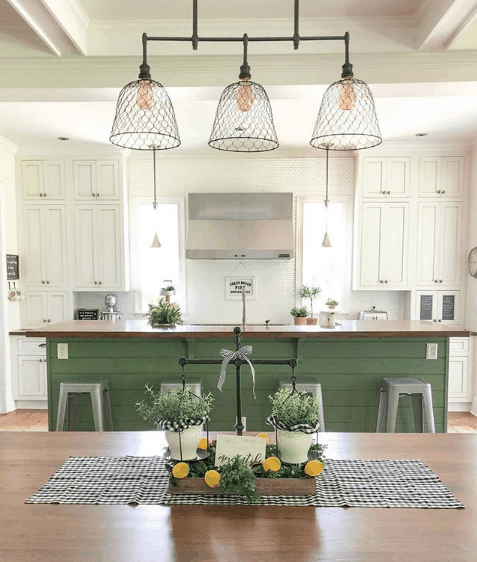A kitchen where the island is painted Sherwin Williams Basil and the rest of the cabinetry is a creamy white.
