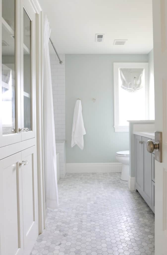 A bathroom with lots of marble, white cabinetry and Sea Salt on the walls.