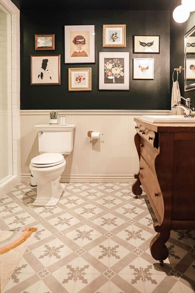This bathroom has accessible beige on the beadboard on the bottom half of the wall with black paint above.