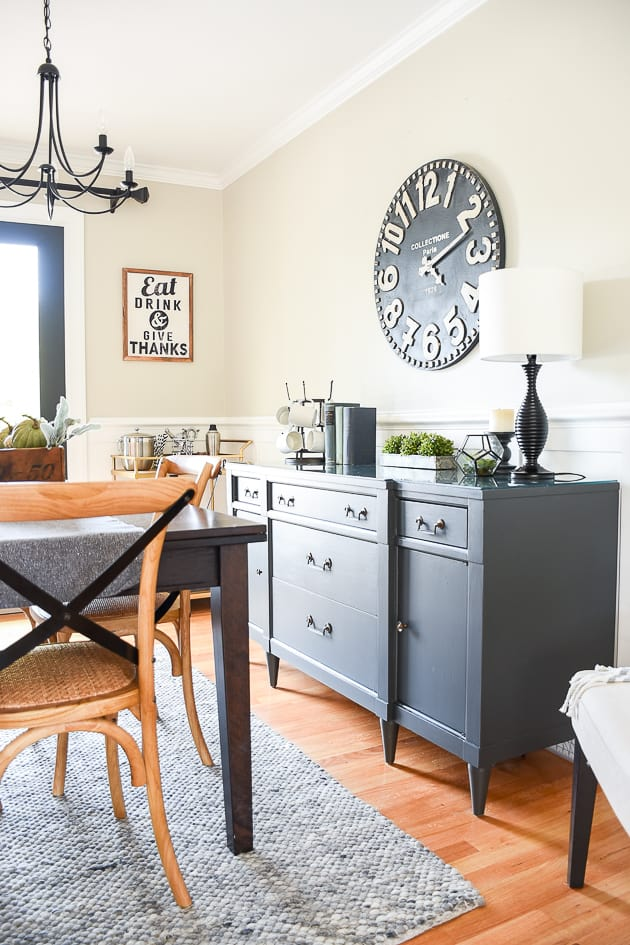 This dining room has black furniture, white wainscoting and accessisble beige on the walls.