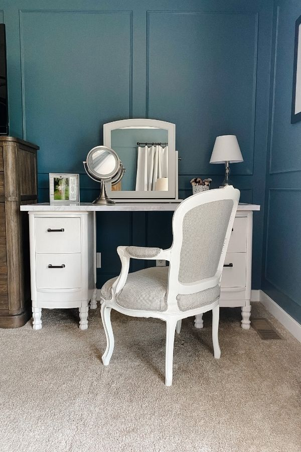 This front view shows my antique vanity makeover with my reupholstered chair and you can see my diy herringbone headboard in the reflection of the mirror.