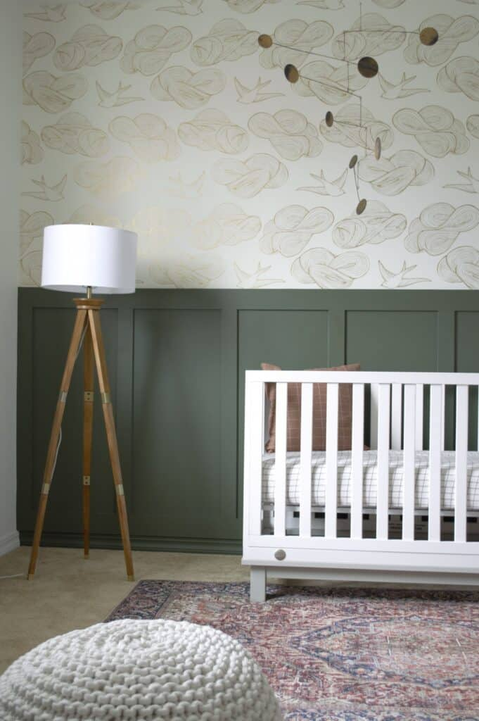 Backwoods used on wainscoting in a nursery with a white crib and wallpaper above.