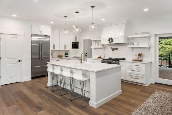 A white kitchen with white counters and white bar stools with silver bases.
