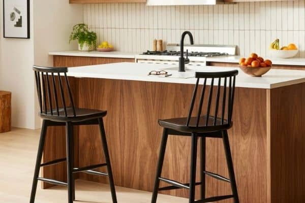 High backed wooden bar stools that have spindles for a back and are painted black.