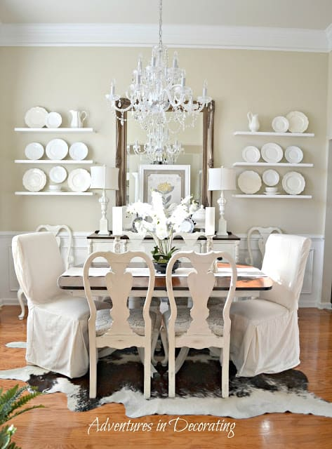 A dining room with all white decor and Manchester Tan walls.