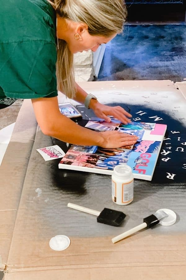 Here my daughter is putting the photos on the canvas after the first coat of mod podge.