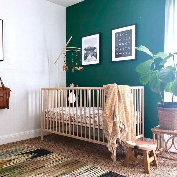A nursery with an accent wall behind a light wooden crib in Evergreens.