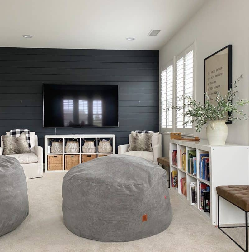 A family room with French Beret painted shiplap on the TV wall and the other walls are white.