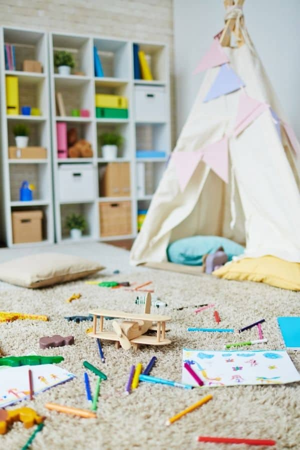 Here is a teepee in a kids play room and lots of toys laying around the floor.